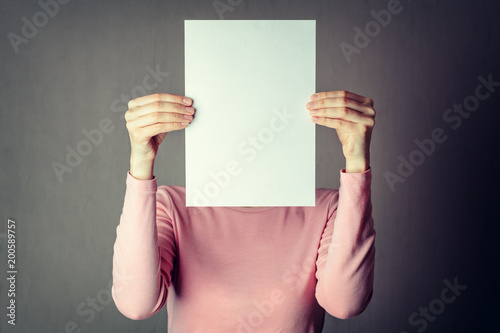 Fotografía  anonymous woman covering face with white paper sheet