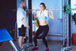 Beautiful woman at the gym exercising with her trainer. Beautiful woman. Gym