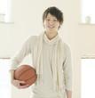 部屋でバスケットボールを持ち微笑む男性