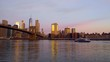 Sunrise over the East River next to the Brooklyn Bridge as a boat floats by with the New York Skyline.