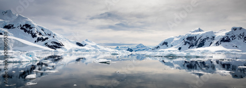 Snow covered mountains reflected on still water with cloudy sky, Paradise Habour, Antarctica