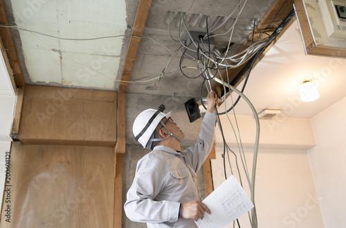 Obraz マンション・スクケルトンリフォーム・電気工事・図面を持ちながらチェックする作業員 - fototapety do salonu