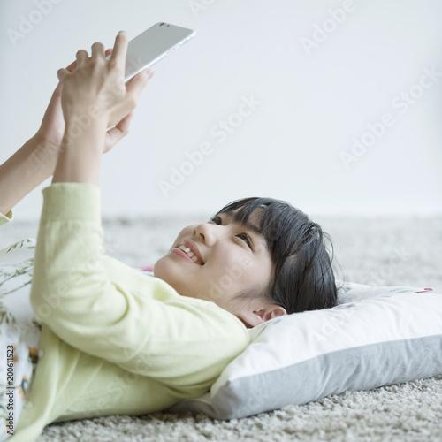 床に寝転びスマートフォンを見る女性