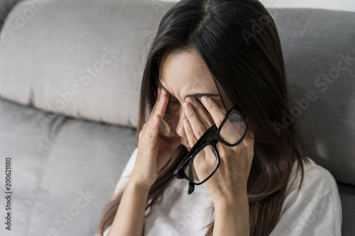 Fotografie, Obraz  Young woman take off her glasses and siiting on sofa