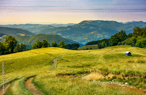 Foto op Canvas Honing truck path down the grassy hill. wooden shed on the hillside. beautiful landscape with Krasna mountain ridge in the distance in evening light. Carpathian mountains, Ukraine