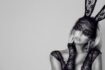 Piękna, seksowna blondynki kobieta w eleganckiej bieliźnie i czarnej koronkowej Wielkanocnego królika masce, stoi na białym tle