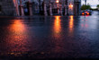 Macro closeup of wet street pavement at night with reflection of golden lantern lights background asphalt