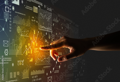 Photo  Female finger touching a beam of light surrounded by charts and graphs
