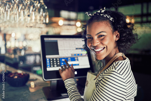Fotografie, Obraz  Smiling African waitress using a restaurant point of sale termin