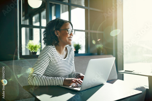 Other Smiling young African woman working online with her laptop