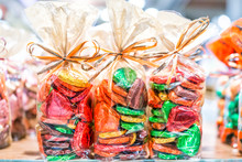 Colorful Packaged Wrapped Chocolate Hearts In Candy Store Shop, Green, Golden, Gold, Yellow As Gifts, Tied In Bags Ribbons Red Foil Holiday Background
