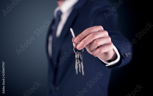 Papiers peints Akt Young businessman hand over keys with empty dark background
