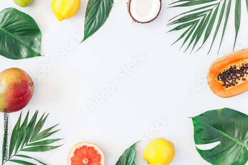 Foto op Plexiglas Vruchten Summer tropical composition. Green palm leaves and tropical fruits on gray background. Summer concept. Flat lay, top view, copy space