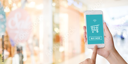 Hand holding smart phone with shopping online device on screen over blue background with copy space, business and technology, online shopping concept
