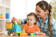 Curly child boy and young woman playing with developmental toy in daycare or kindergarten