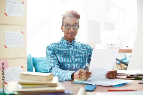 Photo  Young confident student in eyeglasses and shirt reading his essay on paper befor