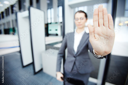 Photo Hand of female security showing stop gesture to someone while standing by gates