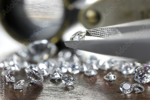 Photo  brilliant cut diamond held by tweezers
