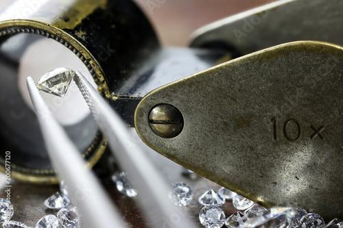 brilliant cut diamond held by tweezers