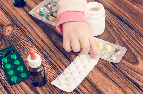 Fotografía  Children's hands with medicines on a wooden table