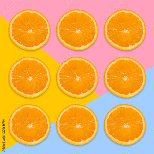 Foto op Canvas Vruchten A pieces of orange on a pink, yellow and blue background. View from above. Contemporary art image