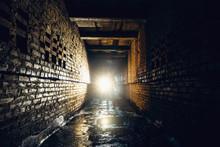 Silhouette Of Man With Flashlight In Dark Dirty Brick Underground Tunnel Or Sewerage Corridor