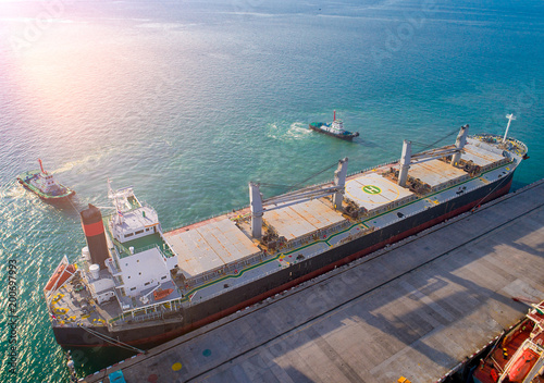 Leinwand Poster aerial view of general bulk cargo ship vessel on departure unberthing from the s
