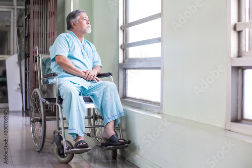 Photo  Asian old man sit on wheelchair looking out to other place