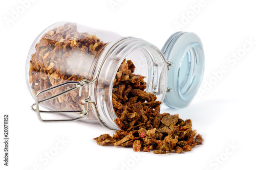Propolis granules poured out of the jar. Isolated on white background. Apitherapy.