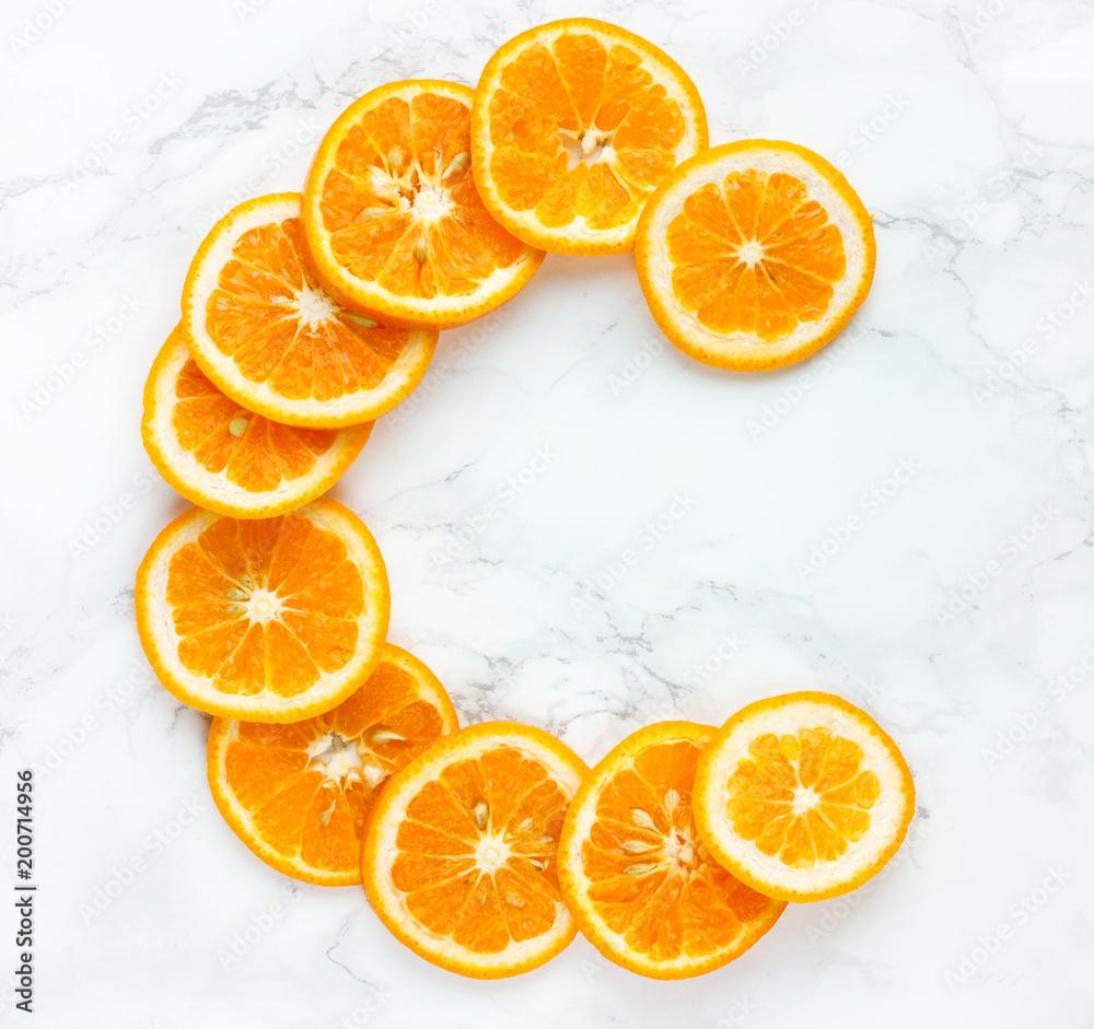 Fototapeta Orange slices vitamin c letter on white background