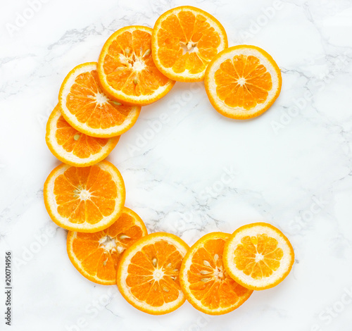 Orange slices vitamin c letter on white background