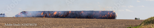 Foto  Stack hay in fire on field with firemans