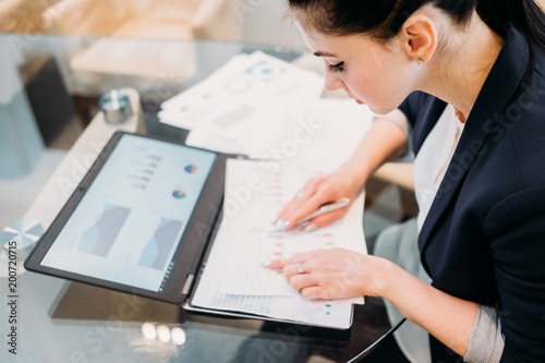 Foto  business analyst studying report papers with graphic results of company activity