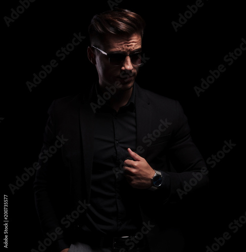 Photo  handsome fashion man looks to side while presenting his watch