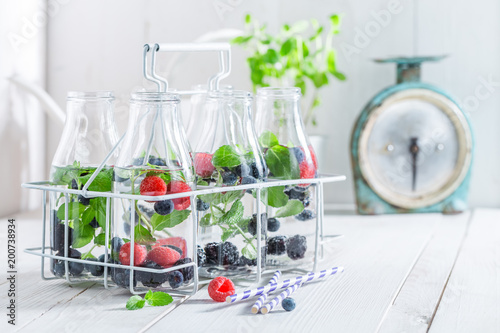 Staande foto Tunesië Healthy water in bottle with berries on white table