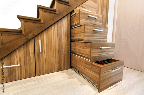 Foto op Canvas Trappen Modern architecture interior with luxury hallway with glossy wooden stairs in modern storey house. Custom built pullout cabinets on glides in slots under stairs