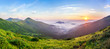 Beautiful sunrise in mountains with white fog below panorama