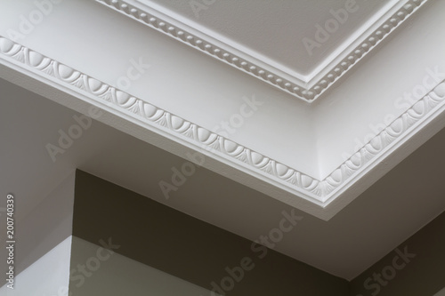 Obraz na plátně Ornamental white molding decor on ceiling of white room close-up detail