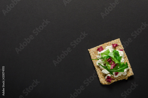 Fotografía  Crisp bread with soft cream cheese and herbs on black background