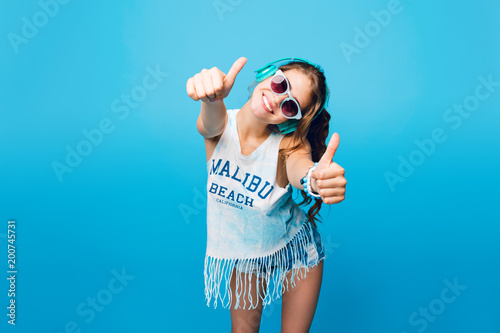 Pretty girl with long curly hair in tail in blue sunglasses  on blue background in studio Canvas Print