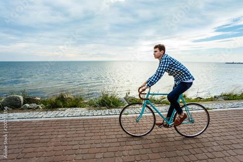 Staande foto Fiets Young man biking at seaside