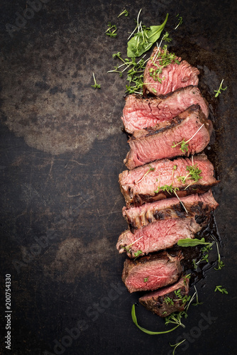 Barbecue wagyu point steak slices with lettuce and herbs as top view on a board with copy space left