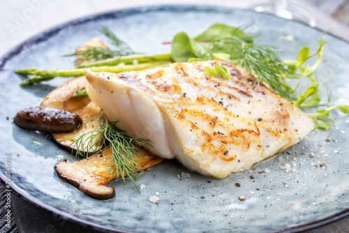 Papiers peints Poisson Fried cod fish filet with green asparagus and mushrooms as close up on a plate