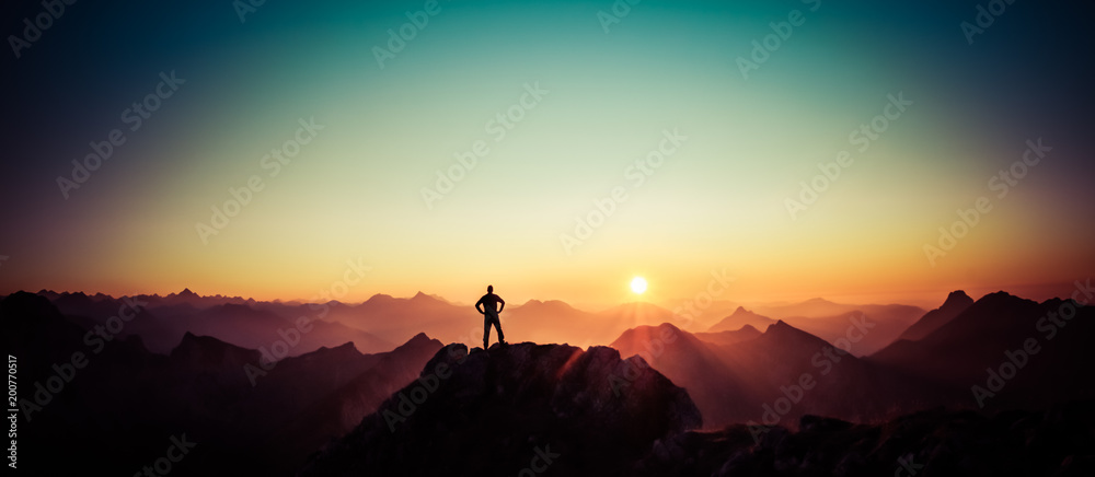 Fototapety, obrazy: Man reaching summit enjoying freedom and looking towards mountains sunrise.
