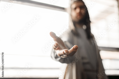 Photo Jesus Christ in white robe reaching out his hand