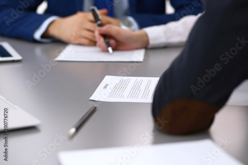 Papiers peints Jardin Group of business people and lawyer discussing contract papers sitting at the table, closeup. Businessman is signing document after agreement done