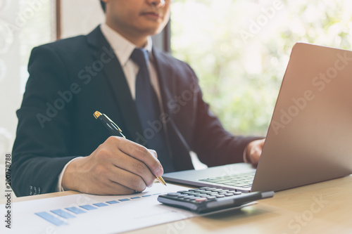 Garden Poster Close up modern businessman writing on chart paper in business documents of graph financial diagram on wooden table and using laptop. Business success, Report, Growth, Marketing plan, Investment.