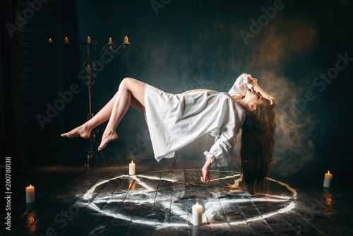 Woman in white shirt flying over pentagram circle Fototapet