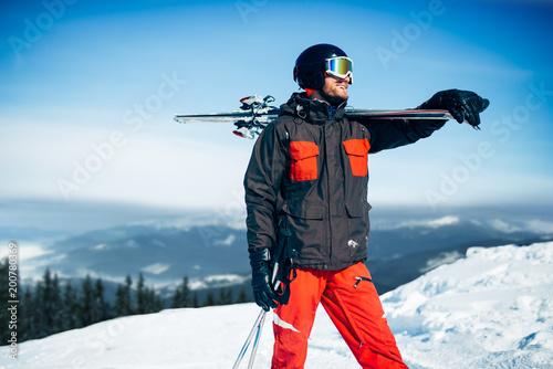 Fotobehang Wintersporten Skier with skis and poles in hands, winter sport