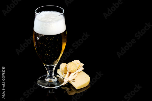 Deurstickers Bar Wineglass of fresh beer with cheese and cheese spheres
